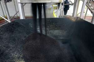 Used coffee grounds pour into a bin for disposal at Aspen Beverage Group, which is one of North America's largest suppliers of cold brew coffee. San Antonio-based GeoJava, an Aspen spin-off, is partnering with Texas A&M University in a two-year study to see how turf grasses respond to coffee grounds used to supplement fertilizers. Coffee grounds are naturally rich in nitrogen, and since the cold brew process doesn't use heat, a lot more of the acidic nutrients are left in the grounds.