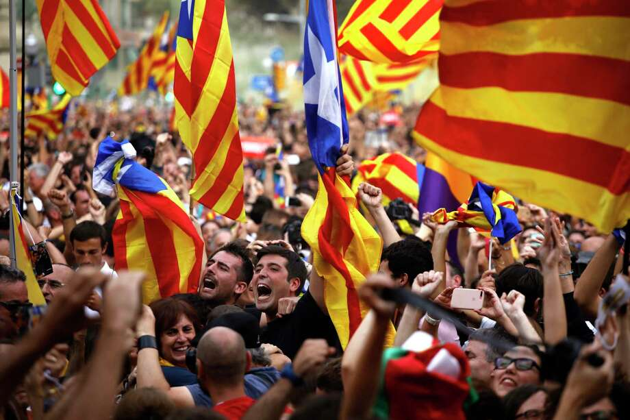 People react as they celebrate the unilateral declaration of independence of Catalonia outside the Catalan Parliament, in Barcelona, Spain, Friday, Oct. 27, 2017. Catalonias' regional Parliament passed a motion Friday to establish an independent Catalan Republic. (AP Photo/ Emilio Morenatti) Photo: Emilio Morenatti, STF / Emilio Morenatti
