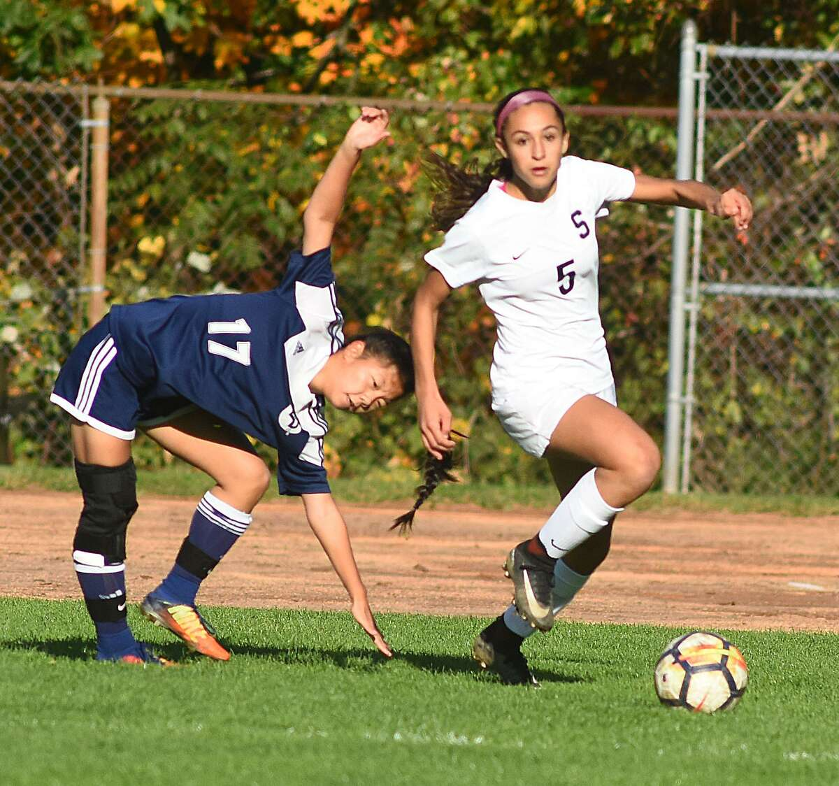 Staples' Julia Lombardo, right, pushes the ball up field as Wilton defender Grave Rava tries to keep her balance during Friday's FCIAC girls soccer quarterfinal game at Loeffler Field in Westport. Staples won 2-0.