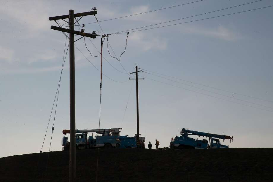 PG&E crews work in Sonoma to restore electricity after the wildfires . The utility will probably be held liable for damages, whether or not it was at fault. Photo: Paul Kuroda, Special To The Chronicle
