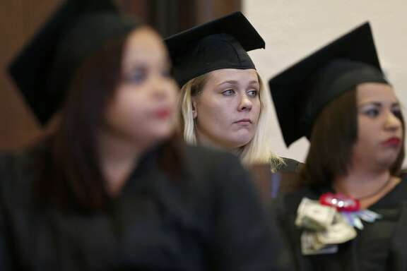 Bexar County Family Drug Court graduate Brianna Smith (center) and others listen to speakers during the 22nd biannual commencement ceremony held Friday Oct. 27, 2017 at the Bexar County Courthouse.