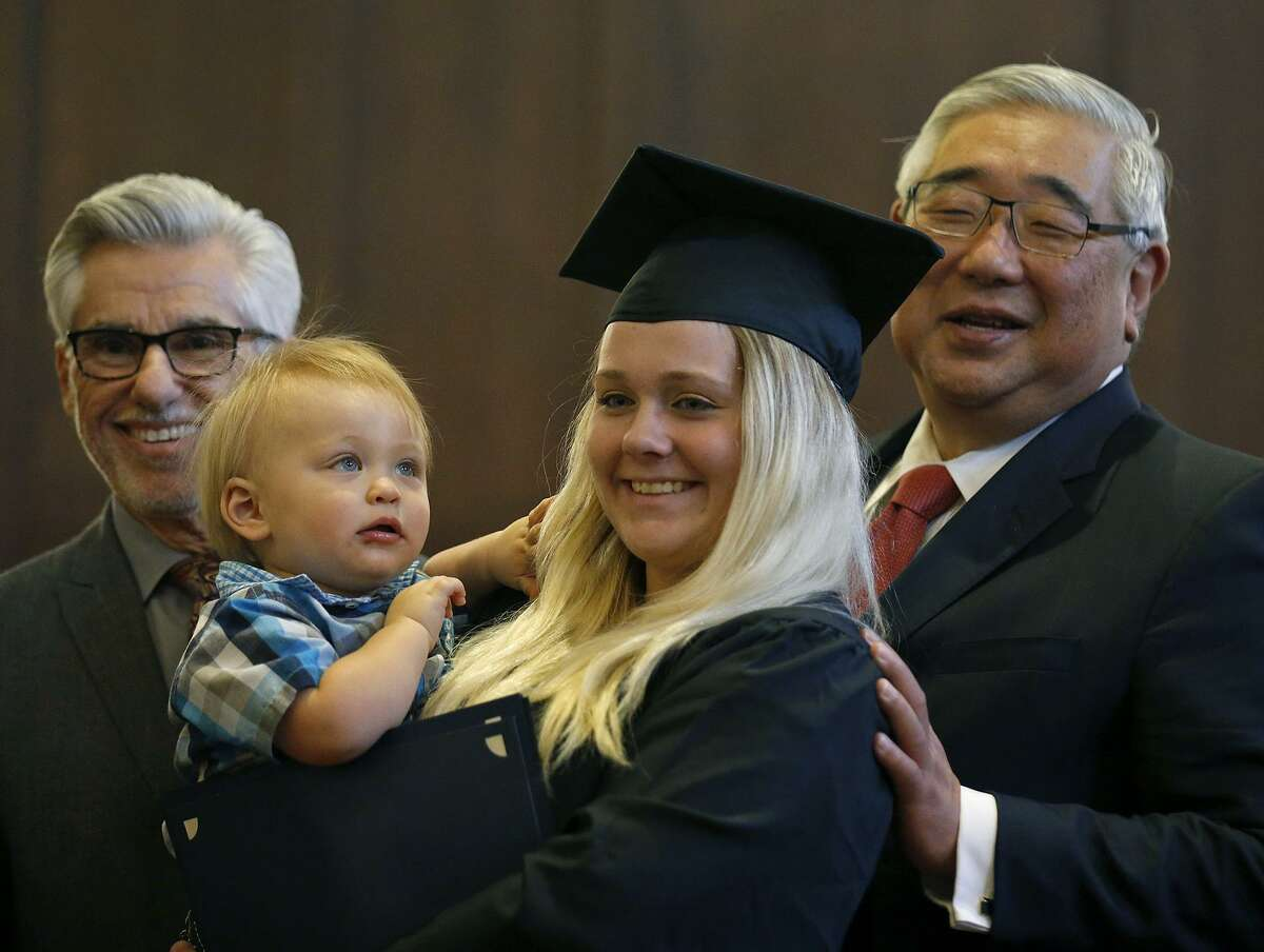 Bexar County Family Drug Court graduate Brianna Smith with her son Zane Urban, 1, (center) poses for photos with Judge Richard Garcia (left) and Judge Peter Sakai during the 22nd biannual commencement ceremony held Oct. 27, 2017 at the Bexar County Courthouse. The special Family Drug Court was formed in 2003, and brought a wealth of treatment to and intensive involvement with parents who have a CPS court case as well as a substance abuse problem.