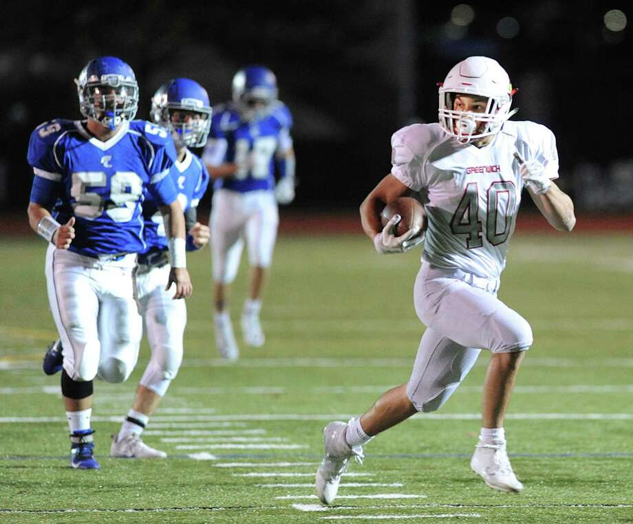 Greenwich running back Tysen Comizio (4 0) runs away f rom Fairfield Ludlowe's Wil Parisi (59) to score a touchdown on a reception from    quarter back Gavin  Muir. Photo: Bob Luckey Jr. / Hearst Connecticut Media / Greenwich Time