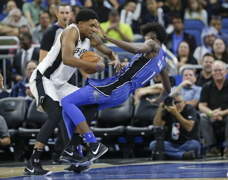 San Antonio Spurs' Rudy Gay, left, is charged with an offensive foul as he runs into Orlando Magic's Jonathan Isaac during the first half of an NBA basketball game, Friday, Oct. 27, 2017, in Orlando, Fla. (AP Photo/John Raoux)
