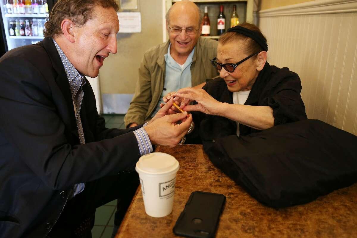 Baer receives an Alamo School pencil from his elementary school teacher, Maria Rondo, at Angelina's Cafe.