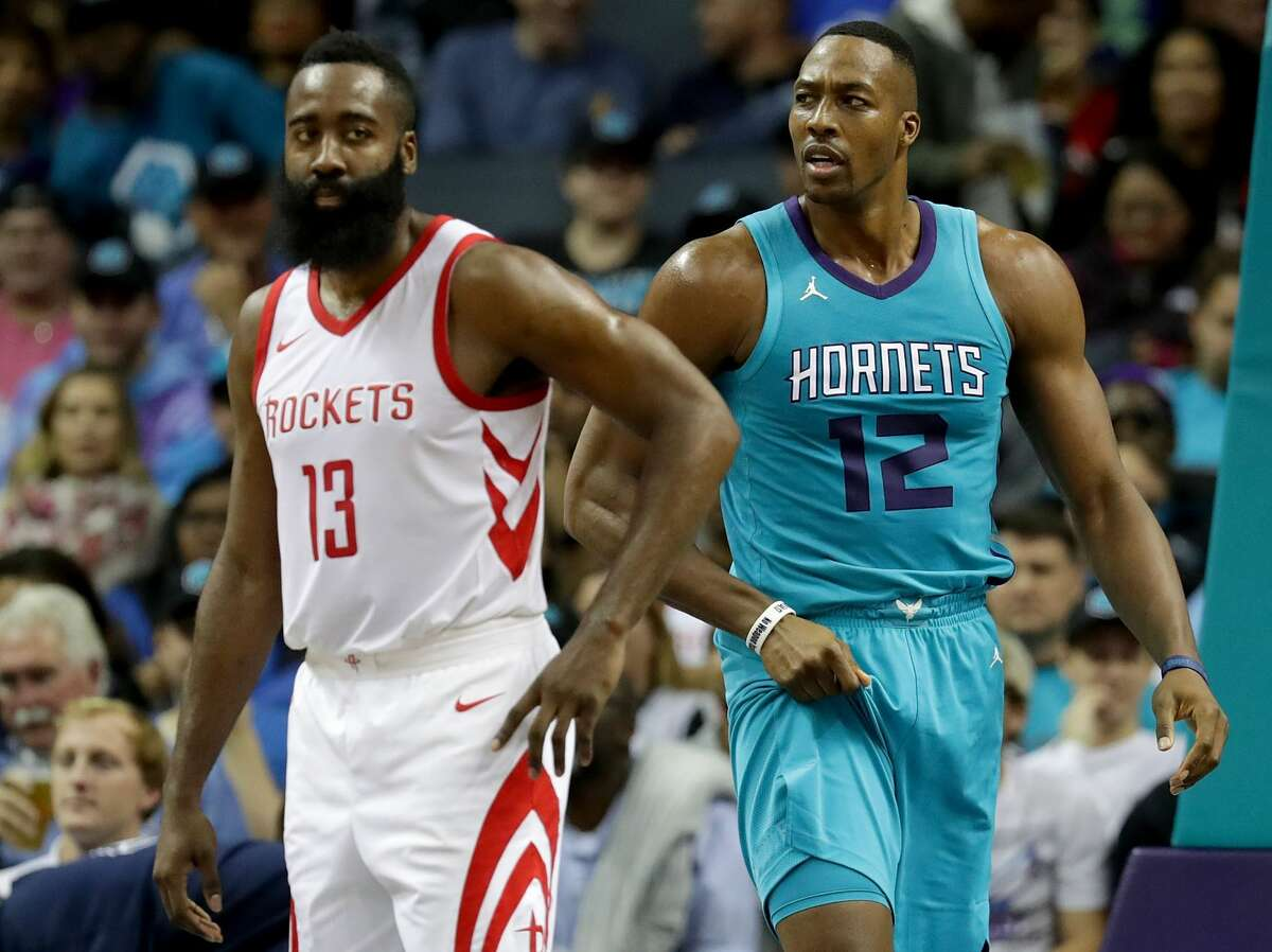 CHARLOTTE, NC - OCTOBER 27: James Harden #13 of the Houston Rockets and Dwight Howard #12 of the Charlotte Hornets watch on during their game at Spectrum Center on October 27, 2017 in Charlotte, North Carolina. NOTE TO USER: User expressly acknowledges and agrees that, by downloading and or using this photograph, User is consenting to the terms and conditions of the Getty Images License Agreement. (Photo by Streeter Lecka/Getty Images)