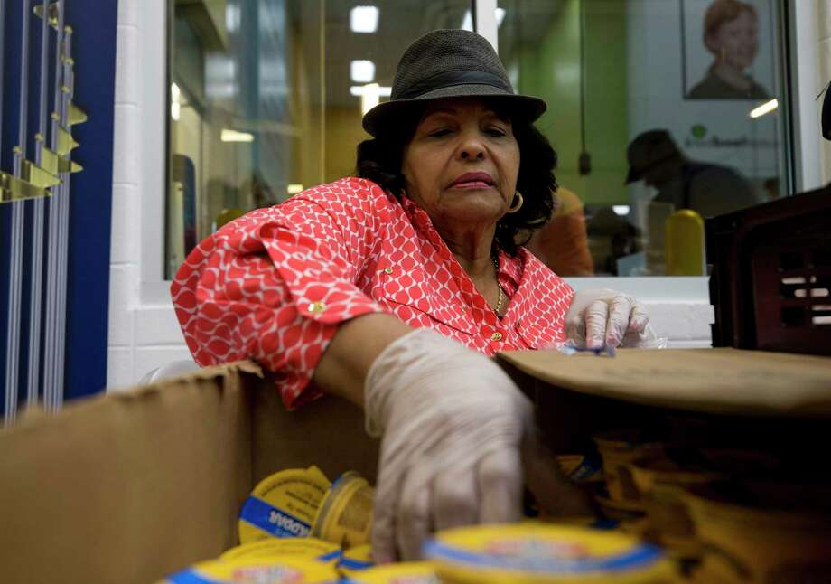 Vera Clemente, widow of Baseball Hall of Famer Roberto Clemente, helps Astros staffers and others pack lunch bags Friday during a volunteer event at the Houston Food Bank Photo: Godofredo A. Vasquez, Houston Chronicle / Godofredo A. Vasquez