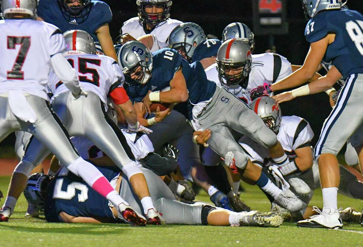 Staples' Harris Levi dives for a first down during Friday's game against Fairfield Warde.