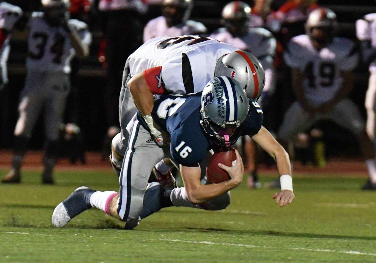 Warde's Jake Hios sacks Staples quarterback Daniel Thompson on Friday night in Westport.