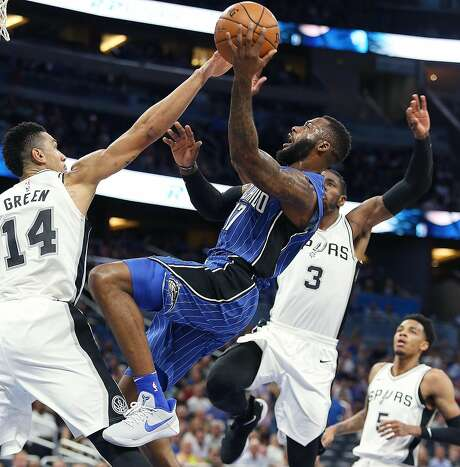 The Orlando Magic's Jonathon Simmons (17) shoots past the San Antonio Spurs' Danny Green (14) and Brandon Paul (3) during the first half at the Amway Center in Orlando, Fla., on Friday, Oct. 27, 2017. (Stephen M. Dowell/Orlando Sentinel/TNS) Photo: Stephen M. Dowell, TNS