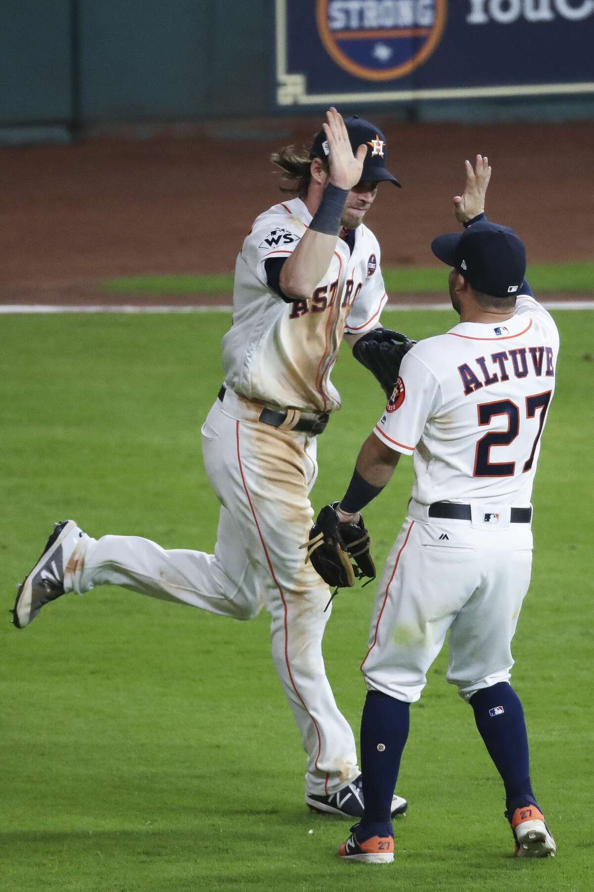 Houston Astros second baseman Jose Altuve (27) high fives right fielder Josh Reddick (22) after Reddick caught the last out of the ninth inning as the Houston Astros beat the Los Angeles Dodgers 5-3 in Game 3 of the World Series at Minute Maid Park Friday, Oct. 27, 2017 in Houston.