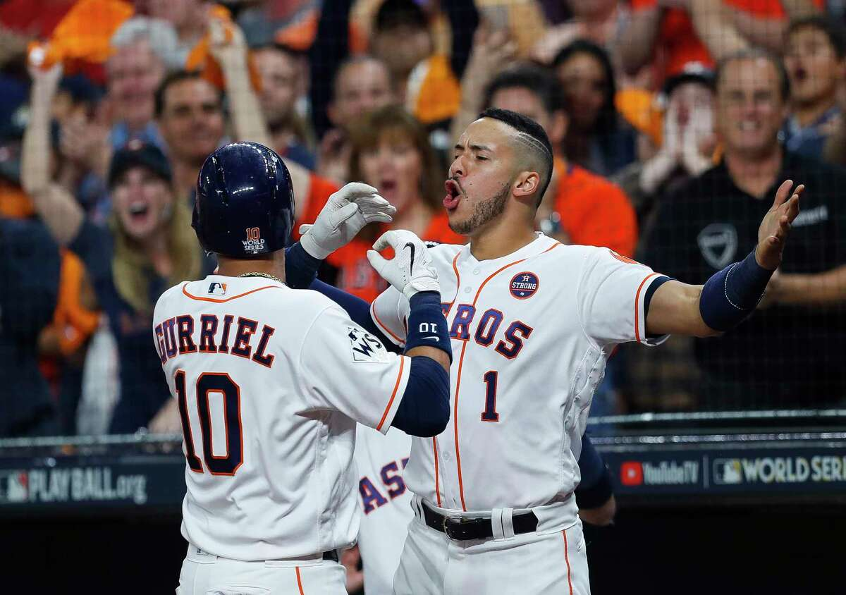 Yuli Gurriel, left, enjoys his home run in the second inning of Game 3 with Astros teammate Carlos Correa on Friday night at Minute Maid Park. The blast to left field provided the first run in the Astros' 5-3 victory.