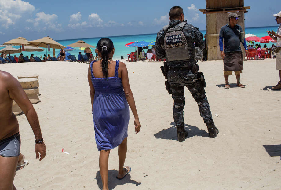 A federal Police officer patrols a beach in Cancun on July 11. Photo: Bloomberg Photo By Brett Gundlock. / Bloomberg