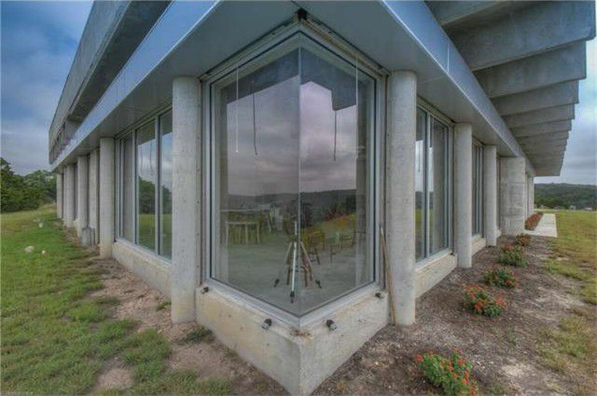 A little more than an hour's drive from San Antonio, near Leakey, sits this concrete and glass Brutalist style home built into a hillside. Asking price is $949,00.