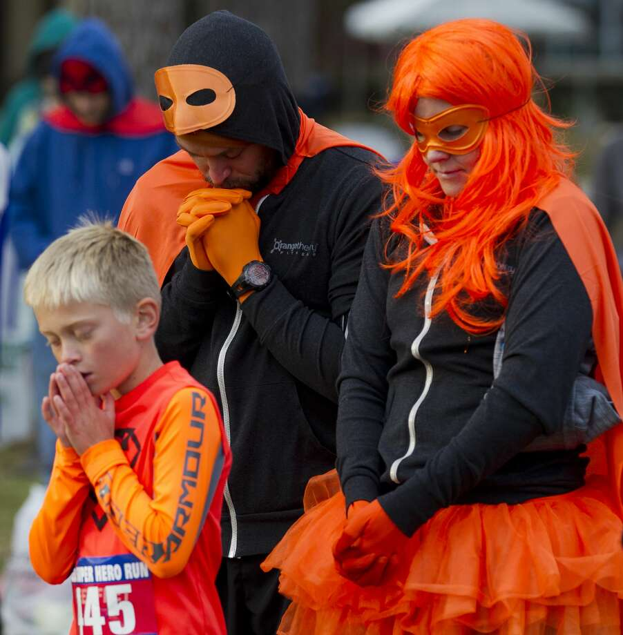 Keri Desautels, right prays with her son Sage alongside Derrick Martin before the annual CASA Superhero Run at The Woodlands Christian Academy, Saturday, Oct. 28, 2017, in The Woodlands. Photo: Jason Fochtman/Houston Chronicle