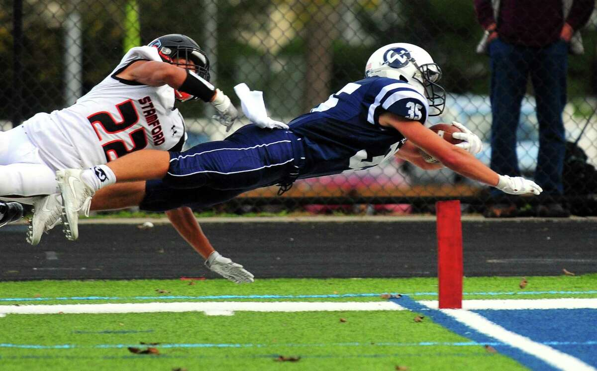 Wilton's Drew Herlyn dives in an attempt to reach the end zone during football action against Stamford in Wilton, Conn. on Saturday Oct. 28, 2017. Herlyn fell short in the attempt. At left is Stamford's Julius Page.