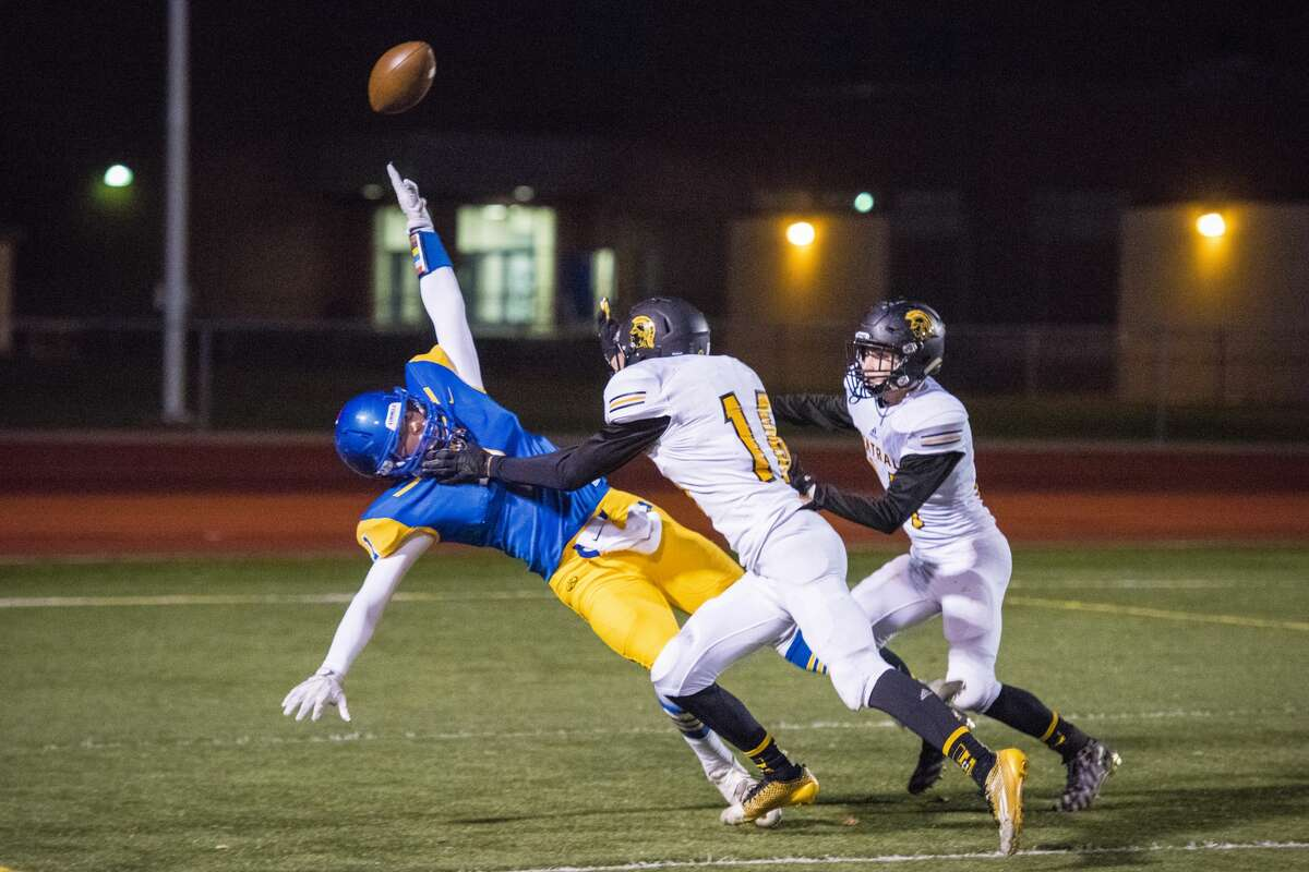 Midland senior Mitchell Reid falls as Traverse City Central junior Ike Battle tackles him before Reid can catch a pass during the district semifinals against Traverse City Central on Friday, Oct. 27, 2017 in Midland. (Danielle McGrew Tenbusch/for the Daily News)