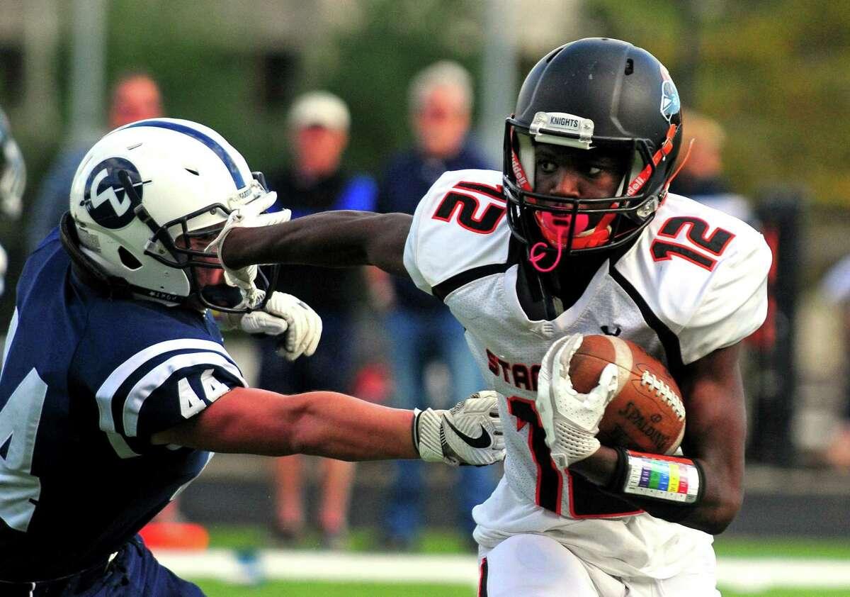 Stamford's Lguenskee Saint Louis tries to push away Wilton's Tyler Previte during football action in Wilton, Conn. on Saturday Oct. 28, 2017.