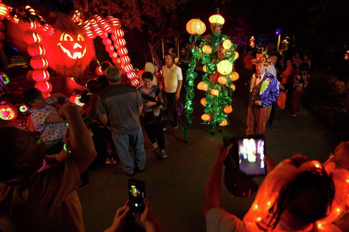 This Sept. 28, 2017 photo shows a giant pumpkin spider and guests near one of Dollywood's Great Pumpkin LumiNights displays in Pigeon Forge, Tenn. The family friendly nighttime event is new to Dollywood this year. (Steven Bridges/The Dollywood Company via AP)