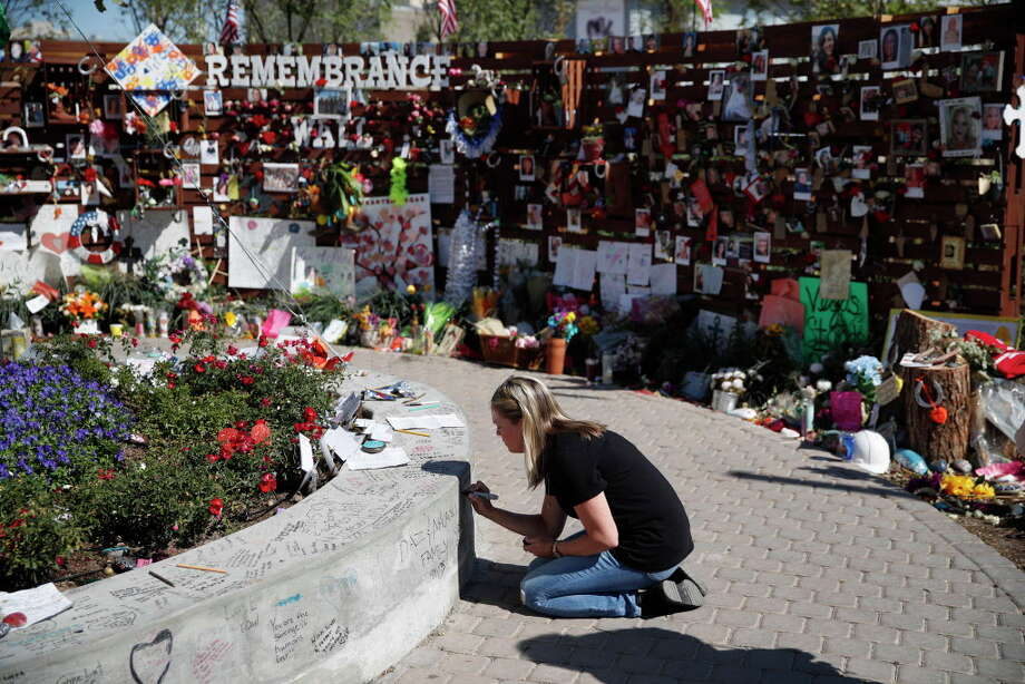 Jenni Tillett writes a message at a Las Vegas memorial for the victims of the recent mass shooting. Photo: John Locher, STF / Copyright 2017 The Associated Press. All rights reserved.