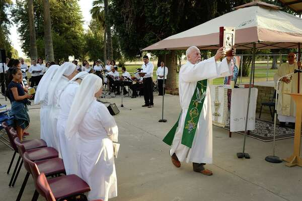 Deacon Ed Valdez carries the Bible during a Mass held at Kearney Park in Fresno, Calif.
