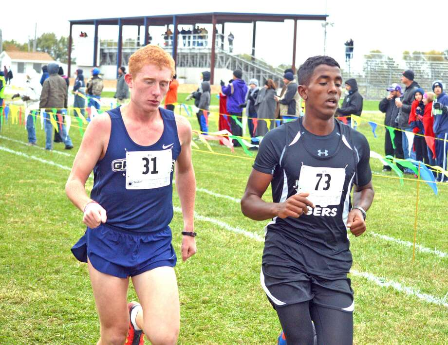 Father McGivney freshman Ross Bushur, left, runs during the first mile of Saturday's Class 1A Carlinville Sectional.