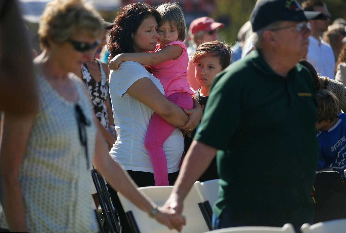 Esmeralda Bishop holds her daughter Alyssa, 5, as her son Brandon, 10, stands next to her while a bell is rung for every life lost during the Sonoma County Day of Remembrance at Santa Rosa Junior College Oct. 28, 2017 in Santa Rosa, Calif. The day memorialized those lives and homes lost in the devastating fires that ripped through the community mere weeks before, killing dozens and destroying thousands of structures, displacing hundreds of people.