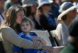 Laura Schulze holds her son Zachary, 8, during the Sonoma County Day of Remembrance at Santa Rosa Junior College Oct. 28, 2017 in Santa Rosa, Calif. The day memorialized those lives and homes lost in the devastating fires that ripped through the community mere weeks before, killing dozens and destroying thousands of structures, displacing hundreds of people.