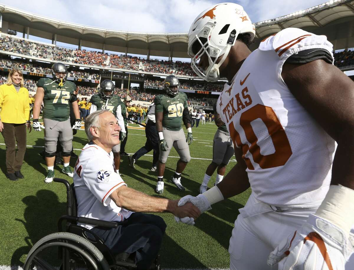 Texas Governor Greg Abbott, left, shakes hands with Texas linebacker Naashon Hughes, right, before an NCAA college football game with Baylor, Saturday, Oct. 28, 2017, in Waco, Texas. Texas won 38-7.(AP Photo/Rod Aydelotte)