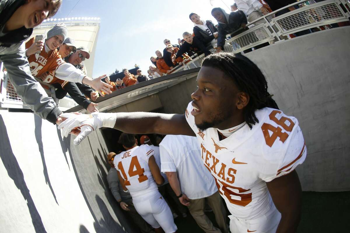 WACO, TX - OCTOBER 28: Malik Jefferson #46 of the Texas Longhorns celebrates with a fan following Texas' 38-7 win over the Baylor Bears at McLane Stadium on October 28, 2017 in Waco, Texas. (Photo by Ron Jenkins/Getty Images)