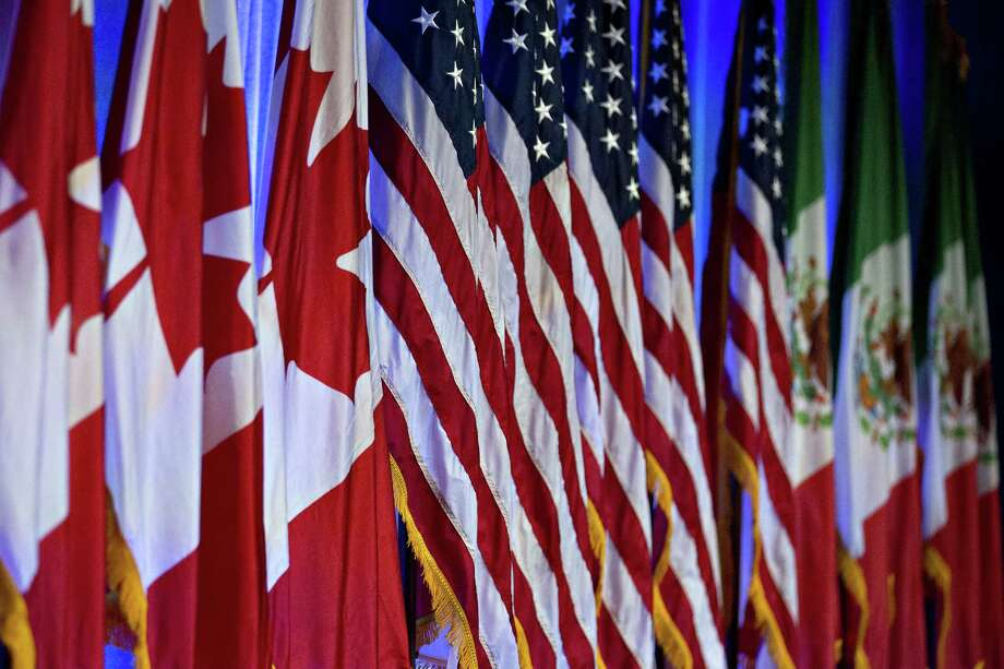 Canadian, American and Mexican flags on stage ahead of the first round of NAFTA renegotiations. Photo: Andrew Harrer / Internal
