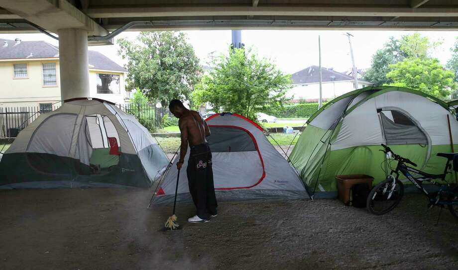 A man sweeps the area around his tent at an encampment under the U.S. 59 overpass near La Branch. Nearby residents say some transients are making life a living hell for those whose homes are immediately adjacent to the encampment. Photo: Yi-Chin Lee, Staff / © 2017  Houston Chronicle