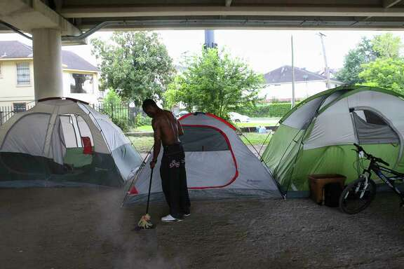 A man sweeps the area around his tent at an encampment under the U.S. 59 overpass near La Branch. Nearby residents say some transients are making life a living hell for those whose homes are immediately adjacent to the encampment.