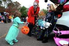 """Stacy Fappiano, of Seymour, gives a Halloween treat to Ella Stugard, 1, of Seymour, during the Town of Seymour's 7th annual """"Trunk or Treat"""" event, where hundreds of trick or treaters will go trunk to trunk to get their candy in the parking lot at Seymour Middle School in Seymour, Conn. on Saturday Oct. 28, 2017. At right is Stacy's daughter Lily, 6. The town's EMT, fire, and police had emergency vehicles were on display, free hot dogs and snacks, a DJ played music and even a Halloween Parade was held with prizes awarded."""