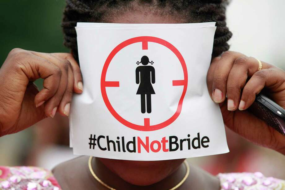 FILE- In this Saturday, July 20, 2013, file photo, a woman protests against underage marriage in Lagos, Nigeria. Child marriage affects nearly 15 million girls around the world, and West and Central Africa has six of the 10 countries with the highest rate. (AP Photo/Sunday Alamba, File) Photo: Sunday Alamba, STF / Copyright 2017 The Associated Press. All rights reserved.