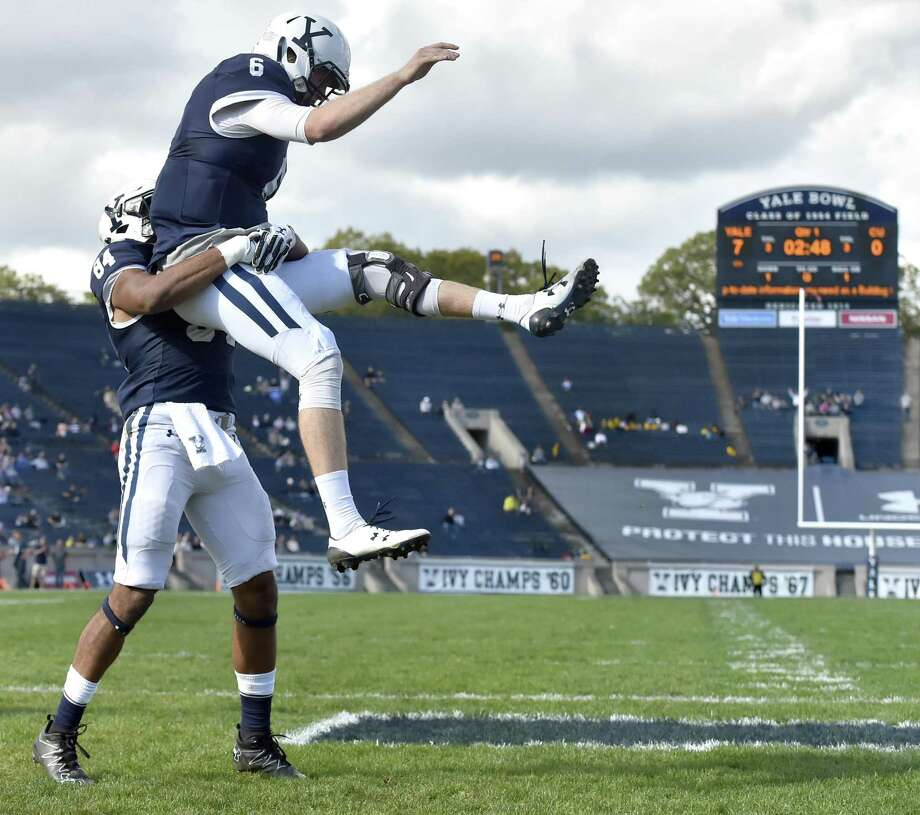 Yale quarterback Kurt Rawlings, right, and wide receiver Christopher Williams-Lopez celebrate the Bulldogs' second touchdown against Columbia in the first quarter Saturday at Yale Bowl. Photo: Peter Hvizdak / Hearst Connecticut Media / New Haven Register