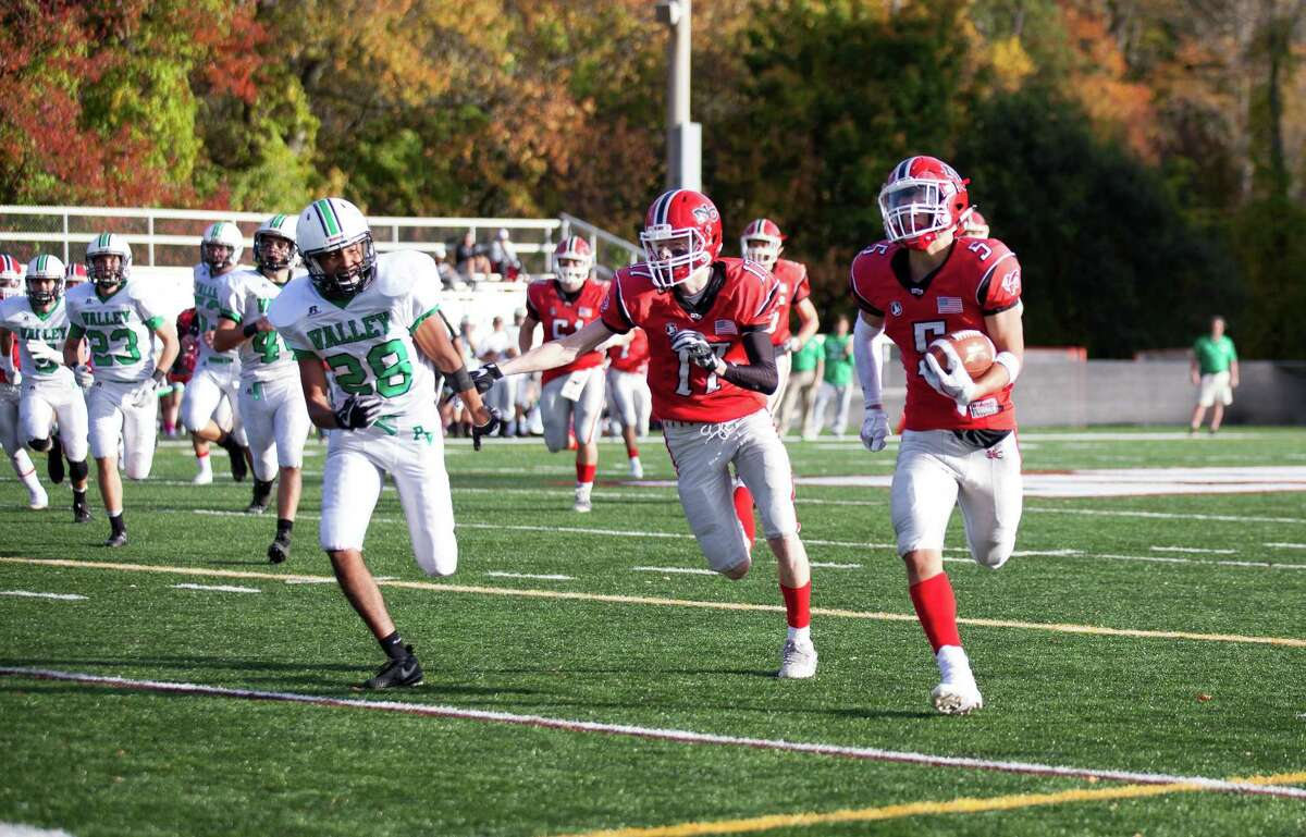 New Canaan's Owen Shin (5) runs downfield as Wyatt Wilson (17) looks to throw a block during a football game between New Canaan and Pascack Valley of New Jersey on Saturday, Oct. 28, 2017 at Dunning Stadium in New Canaan, Conn. New Canaan defeated Pascack Valley 33-14.