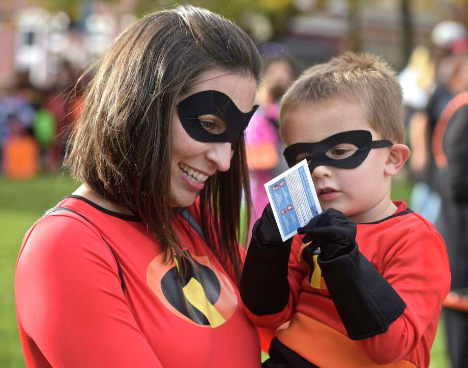 Emerson Payne, 2 1/2, shows his mother Kristen a Danbury Westerners baseball card at the 25th Halloween on the Green. They were dressed as characters from the Incredibles movie. The event was sponsored by the Kiwanis of Danbury, Danbury Jaycees and CityCenter Danbury. Saturday, October 29, 2017, in Danbury, Conn. Photo: H John Voorhees III, Hearst Connecticut Media / The News-Times