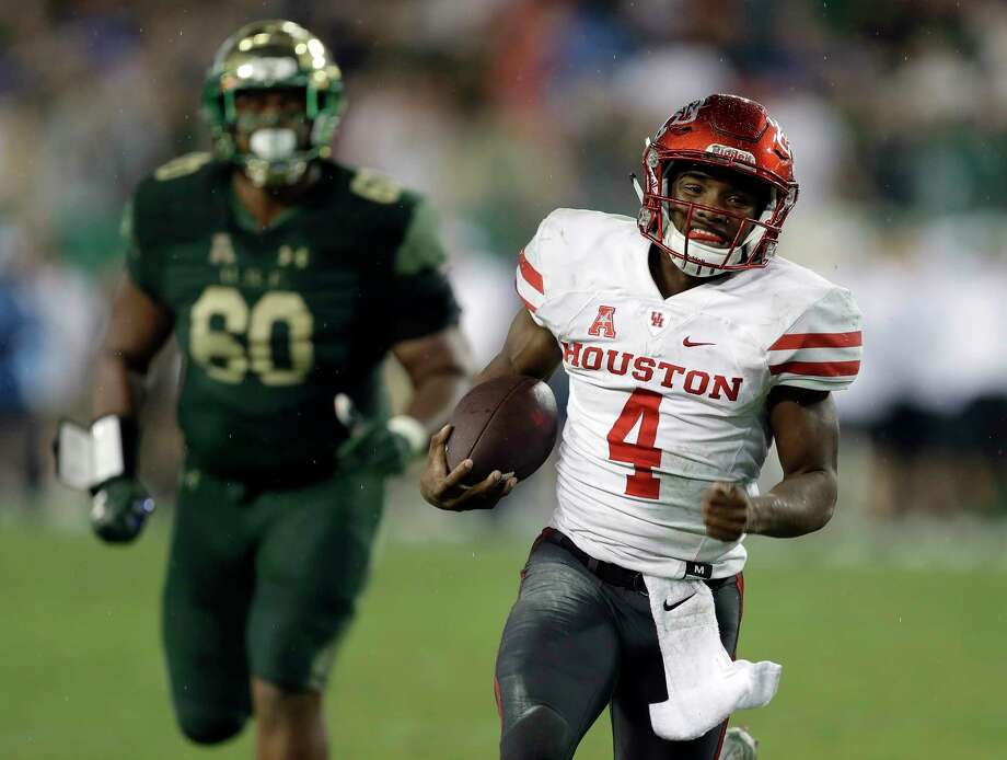 After UH quarterback D'Eriq King, below, breaks free for a go-ahead 20-yard touchdown run in the final seconds, the former Manvel star is mobbed by happy teammates in the end zone Saturday Photo: Chris O'Meara, STF / Copyright 2017 The Associated Press. All rights reserved.