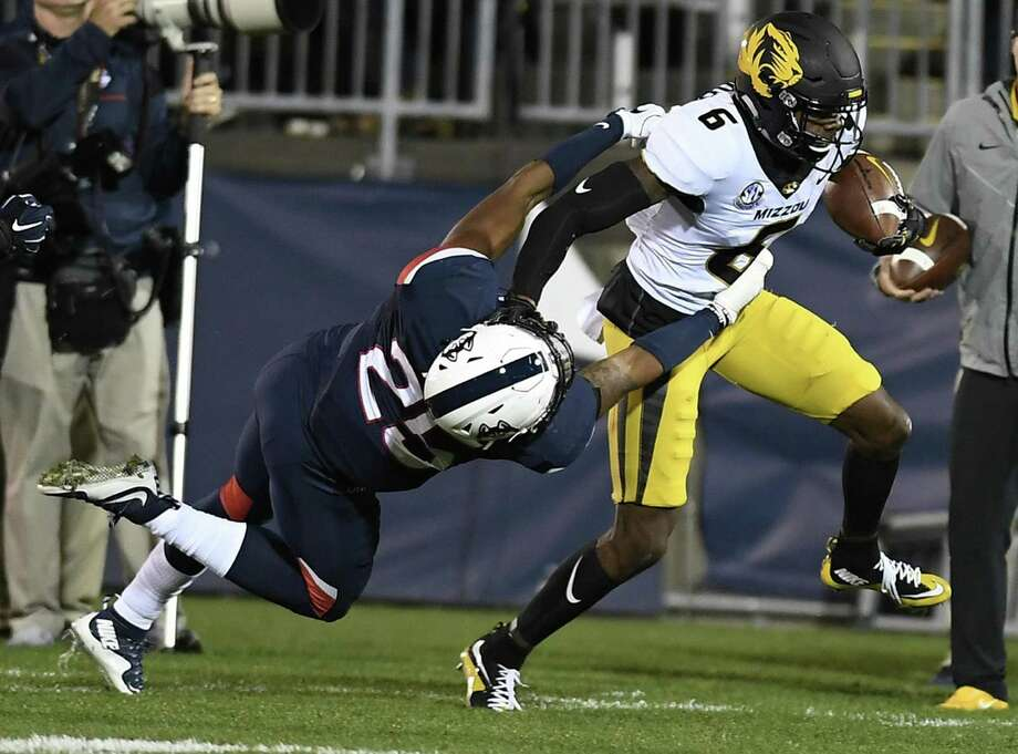 UConn defensive back Tyler Coyle, left, tackles Missouri receiver J'Mon Moore during the first half Saturday. Photo: Jessica Hill / Associated Press / AP2017