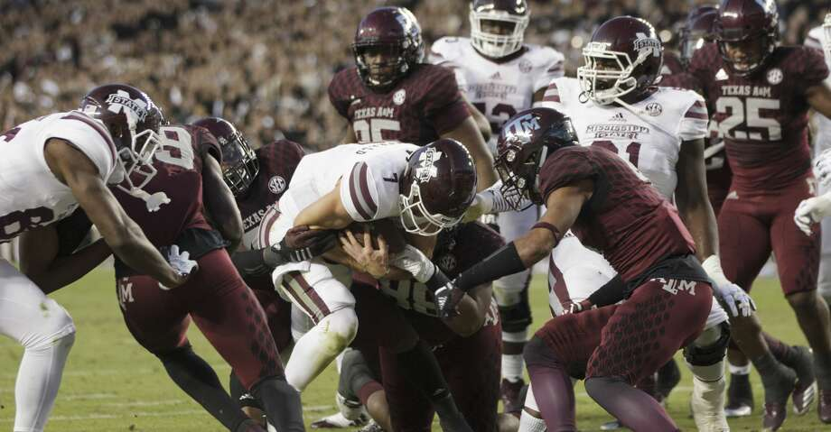 Mississippi State quarterback Nick Fitzgerald (7) cross the goal line for a touchdown as Texas A&M defensive lineman Landis Durham (46) and Kingsley Keke (88) defend during the first quarter of an NCAA college football game on Saturday, Oct. 28, 2017, in College Station, Texas. (AP Photo/Sam Craft) Photo: Sam Craft/Associated Press