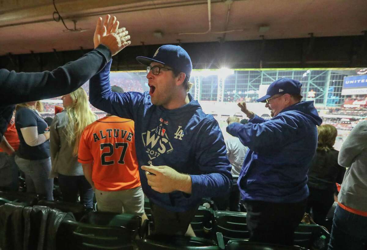 Dodgers fans Ryan Daly and his father, John (right), celebrate after LA's Joc Pederson hit a homer in the 9th inning of World Series Game 4 Saturday, Oct. 28, 2017, in Houston.