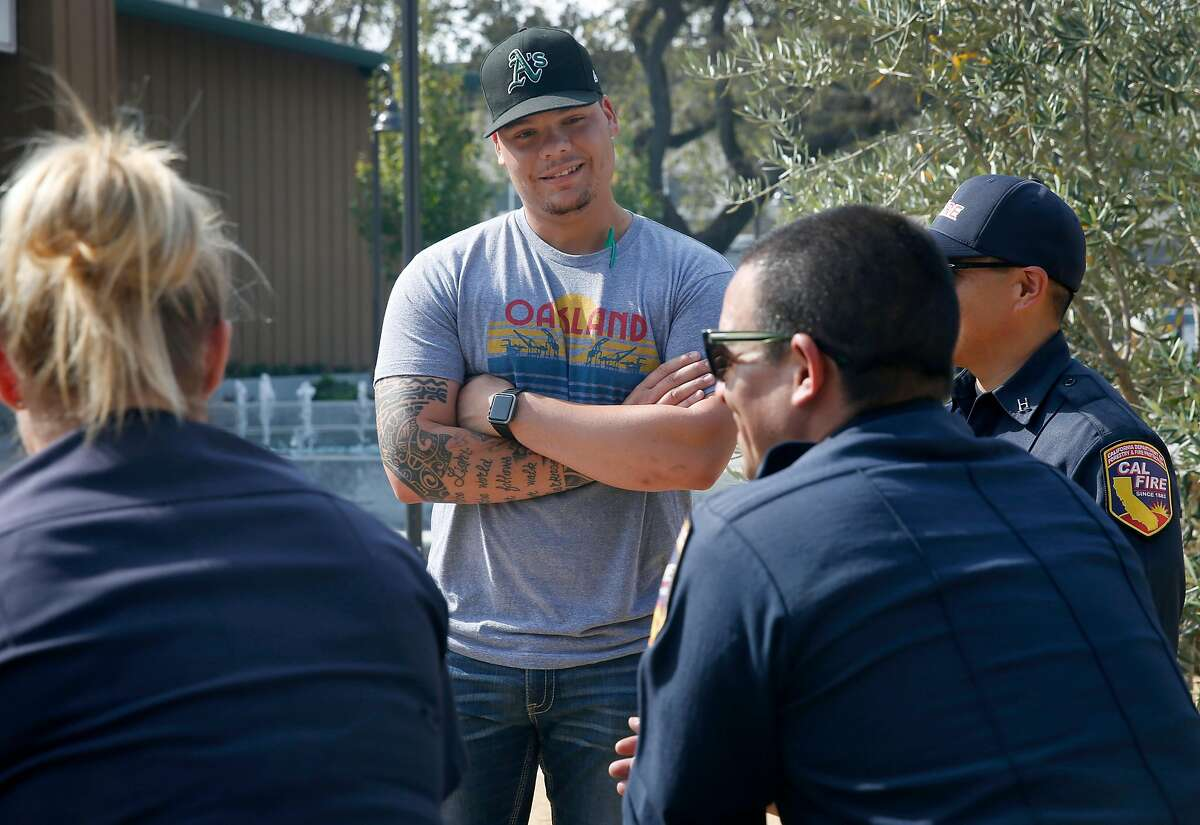 Oakland A's catcher Bruce Maxwell visits with firefighters in the Cal Fire base camp at the Sonoma County Fairgrounds in Santa Rosa, Calif. on Tuesday Oct. 17, 2017.