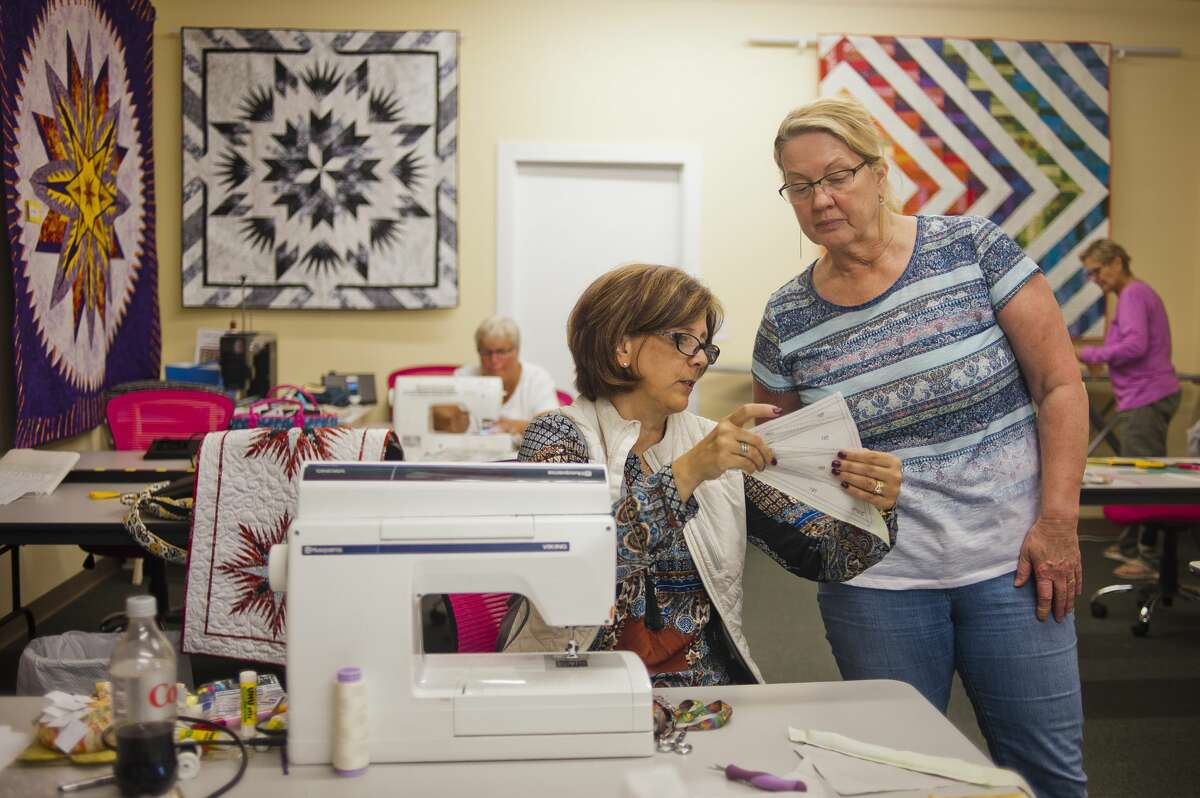 Patty Rapanos, co-owner of Park Bench Quilt Shop, left, assists Nancy Raythatha of Cass City during a quilting class on Wednesday, Oct. 11, 2017. (Katy Kildee/kkildee@mdn.net)
