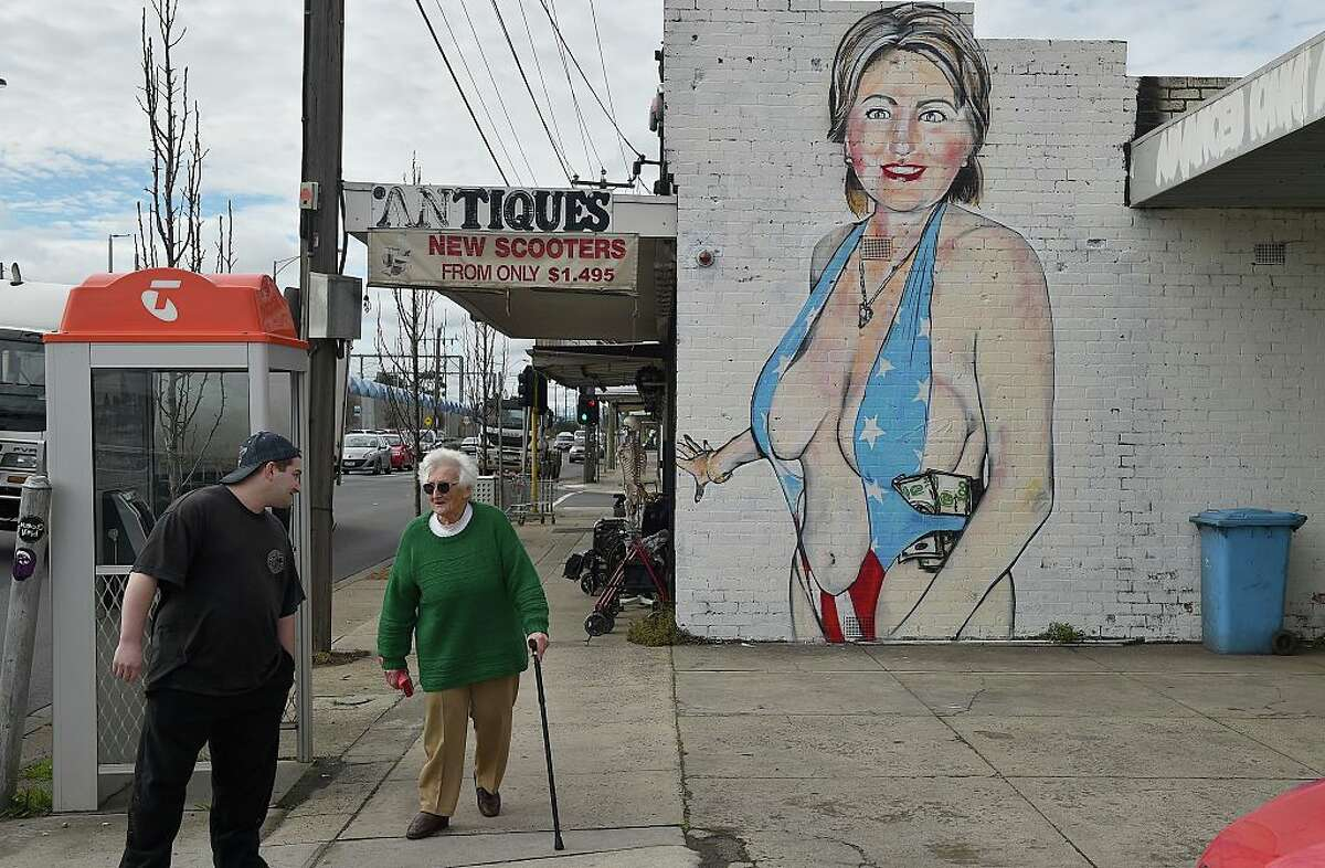 Pedestrians walk past a mural of Democrat US presidential nominee Hillary Clinton clad in a swimsuit, created by street artist Lushsux, in West Footscray in Melbourne on July 30, 2016. An Australian mural of US presidential nominee Hillary Clinton in a revealing, stars and stripes swimsuit may be taken down, after it has reportedly been deemed offensive. / AFP / Paul Crock / RESTRICTED TO EDITORIAL USE - MANDATORY MENTION OF THE ARTIST UPON PUBLICATION - TO ILLUSTRATE THE EVENT AS SPECIFIED IN THE CAPTION (Photo credit should read PAUL CROCK/AFP/Getty Images)