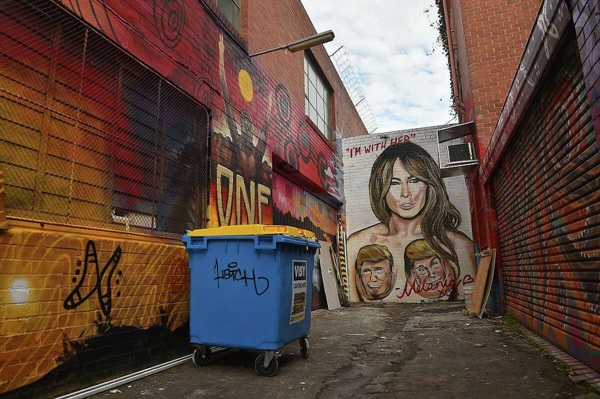 A mural depicting Republican US presidential nominee Donald Trump over the breasts of his wife Melania, created by street artist Lushsux, is seen on a wall in West Footscray in Melbourne on July 30, 2016. An Australian mural of US presidential nominee Hillary Clinton in a revealing, stars and stripes swimsuit may be taken down, after it has reportedly been deemed offensive. The creator of the painting, the street artist who goes by the name Lushsux and who has also painted murals of the likes of Donald Trump and Kim Kardashian, branded calls to remove it