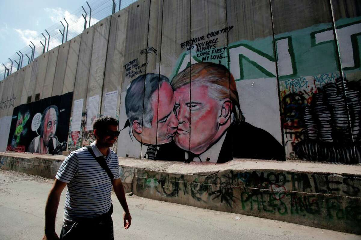 A tourist walks past a graffiti by street artist Lushsux, depicting US President Donald Trump kissing Israeli Prime Minister Benjamin Netanyahu drawn on the controversial Israeli separation barrier separating the West Bank town of Bethlehem from Jerusalem, on October 29, 2017.