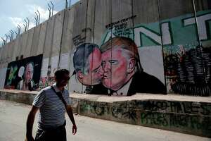 A tourist walks past a graffiti by street artist Lushsux, depicting US President Donald Trump kissing Israeli Prime Minister  Benjamin Netanyahu drawn on the controversial Israeli separation barrier separating the West Bank town of Bethlehem from Jerusalem, on October 29, 2017. / AFP PHOTO / Musa AL SHAER        (Photo credit should read MUSA AL SHAER/AFP/Getty Images)
