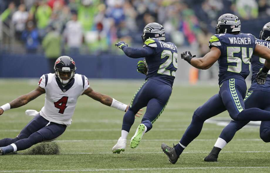 Seattle Seahawks free safety Earl Thomas, second from left, avoids a tackle attempt by Houston Texans quarterback Deshaun Watson (4) after Thomas intercepted a pass from Watson in the first half of an NFL football game, Sunday, Oct. 29, 2017, in Seattle. Thomas returned the interception 78 yards for a touchdown. (AP Photo/Stephen Brashear) Photo: Stephen Brashear/AP