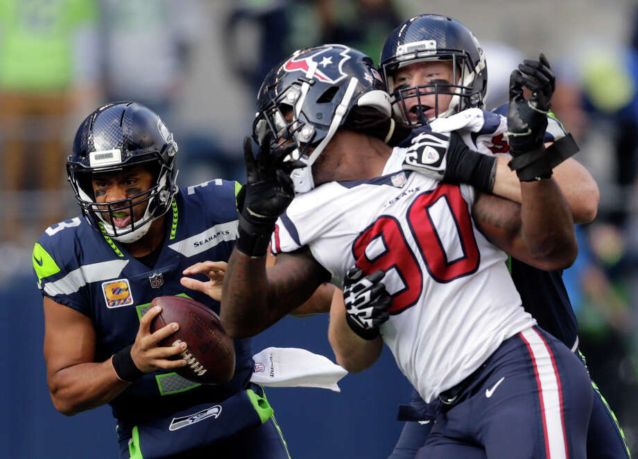 Seattle Seahawks quarterback Russell Wilson, left, keeps the ball as Seattle Seahawks offensive guard Ethan Pocic, right, tries to block Houston Texans outside linebacker Jadeveon Clowney (90) in the second half of an NFL football game, Sunday, Oct. 29, 2017, in Seattle. (AP Photo/Stephen Brashear) Photo: Stephen Brashear/AP